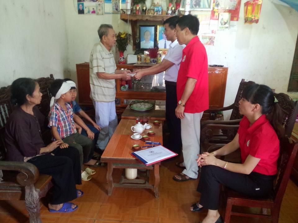 Ông Quách Đức Hùng- Chủ tịch Hội CTĐ tỉnh và ôngLê Tự Huấn - Giám đốc Siêu thị nội thất Trọng Huấn trao tiền hỗ trợ cho gia đình hai cháu Giang Quang Trung và Giang Trung Dũng